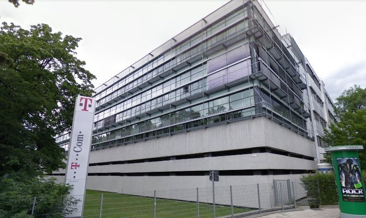 Deutsche Telecom Technical center building showing T Com in front of the boundary fence